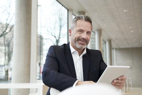 Portrait of smiling businesssman using tablet - FMKF03722
