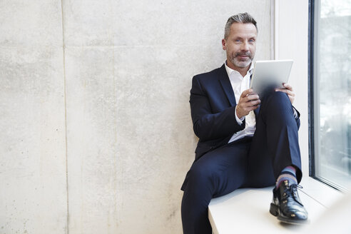 Portrait of smiling businesssman using tablet at the window - FMKF03728