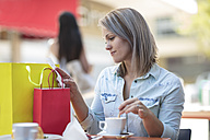 Woman with shopping bags at an outdoor cafe checking bill - ZEF13391