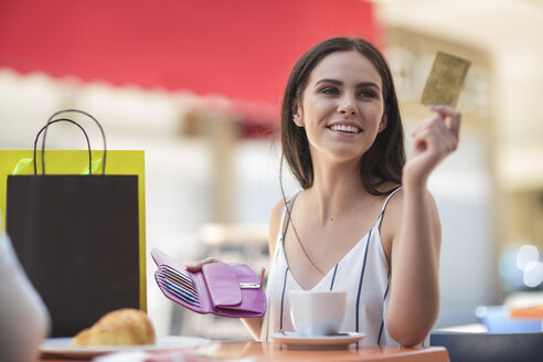 Smiling woman paying with credit card at cafe - ZEF13394
