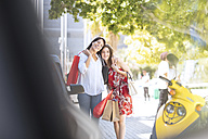 Happy mother and daughter with shopping bags in the city - ZEF13400