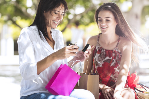 Happy mother and daughter with shopping bags in the city - ZEF13403