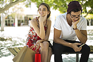 Young couple sitting on bench with shopping bags and cell phone - ZEF13409
