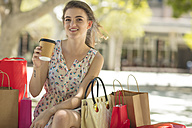 Smiling young woman with shopping bag and takeaway coffee - ZEF13412