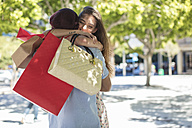 Happy young couple with shopping bags hugging - ZEF13415
