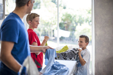 Boys helping father with chores carrying laundry basket - ZEF13423