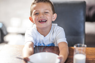 Portrait of smiling boy at dining table - ZEF13429