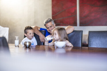 Happy father with children seated having breakfast at table - ZEF13432