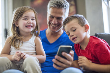 Happy father with children sharing cell phone - ZEF13441