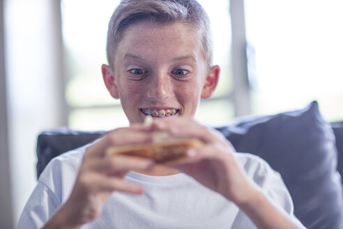 Boy holding sandwich in his hand - ZEF13453