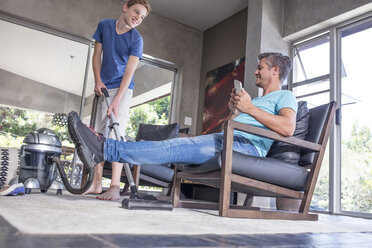 Father relaxing while son vacuuming in living room - ZEF13459