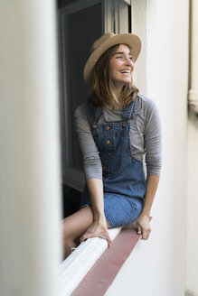 Happy young woman sitting in window frame - KKAF00584