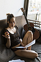 Young woman with music sheets and guitar sitting on couch - KKAF00611