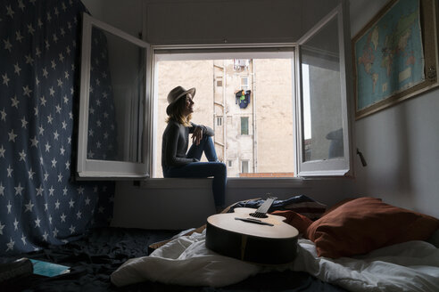 Young woman wearing a hat sitting in window frame - KKAF00632