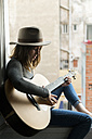 Young woman sitting in window frame playing guitar - KKAF00635