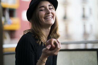 Laughing young woman wearing a hat holding an apple - KKAF00638