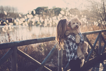 Woman standing on bridge holding her dog - SIPF01499