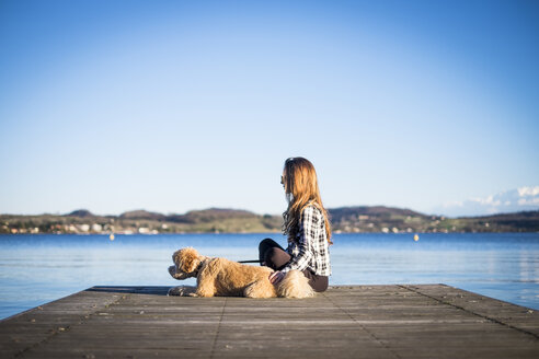 Woman sitting on jetty with her dog - SIPF01505