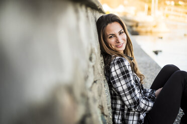 Woman sitting outdoors, leaning on a wall - SIPF01508