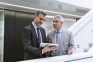 Two businessmen having an informal meeting, using digital tablet - DIGF01566