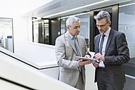 Two businessmen having an informal meeting, using digital tablet - DIGF01572