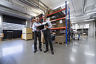 Two businessmen in factory hall talking - DIGF01578
