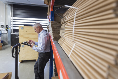 Businessman using tablet in factory hall - DIGF01581
