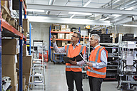 Two colleagues in factory hall wearing safety vests holding clipboard - DIGF01590