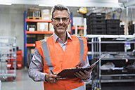 Portrait of smiling man in factory hall wearing safety vest holding clipboard - DIGF01593