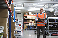 Man in factory hall wearing safety vest holding clipboard - DIGF01596
