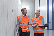 Two colleagues wearing safety vests holding clipboard - DIGF01599