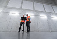 Two colleagues wearing safety vests and hard hats talking in a building - DIGF01602