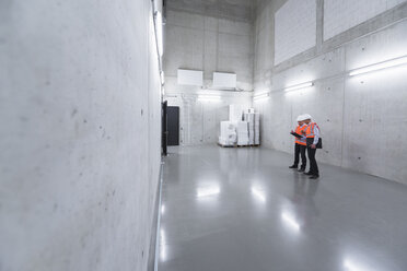 Two colleagues wearing safety vests and hard hats talking in a building - DIGF01605