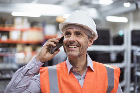 Smiling man in factory hall wearing safety vest and hard hat talking on cell phone - DIGF01608