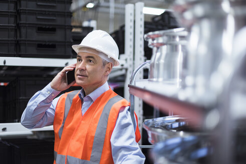 Man in factory hall wearing safety vest and hard hat talking on cell phone - DIGF01611