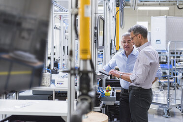 Two businessmen in modern factory hall using computer - DIGF01614