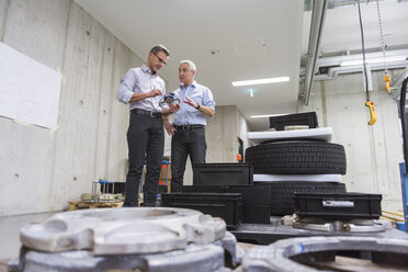 Two businessmen in factory hall with tyres examining product - DIGF01620