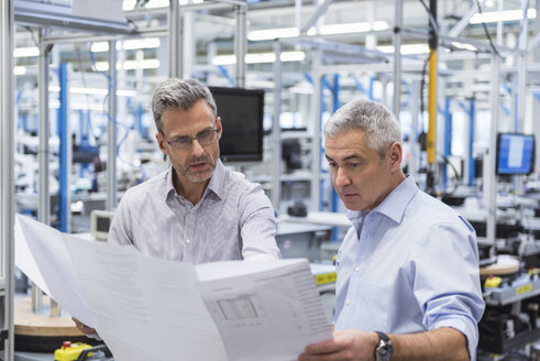 Two businessmen in factory hall discussing construction plan - DIGF01623