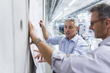 Two businessmen discussing construction plan at concrete wall - DIGF01629