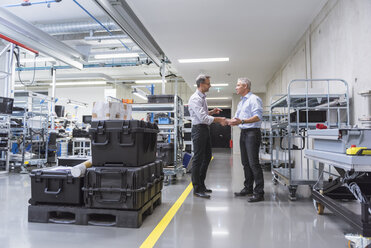Two businessmen shaking hands in factory hall - DIGF01632