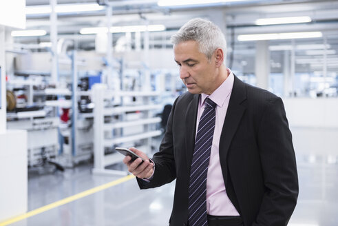 Manager at shop floor of a factory, using smart phone - DIGF01638