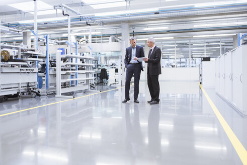 Two mangagers having a meeting at the shop floor of a factory - DIGF01644