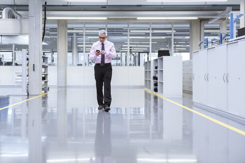 Manager on shop floor of a factory using smart phone - DIGF01653