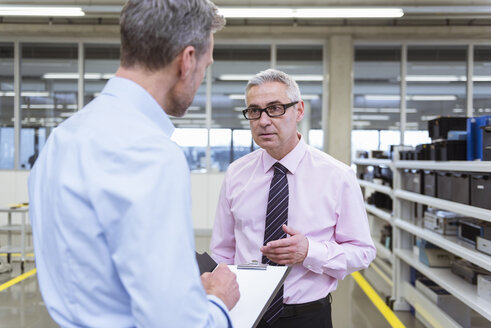 Two mangers discussing on shop floor of company - DIGF01662