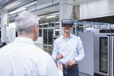Two managers standing in company, using VR goggles - DIGF01698