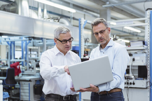Two managers standing in company using laptop - DIGF01701