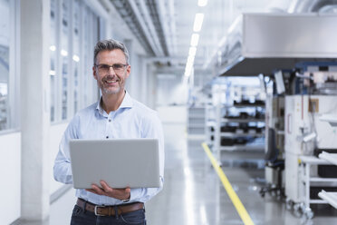 Manager on shop floor of factory using laptop - DIGF01707
