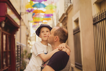 France, Languedoc, Beziers, father kissing son with colorful umbrellas in background - NMSF00035