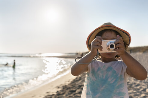 Spain, Menorca, little girl taking a picture on the beach - MGOF03156