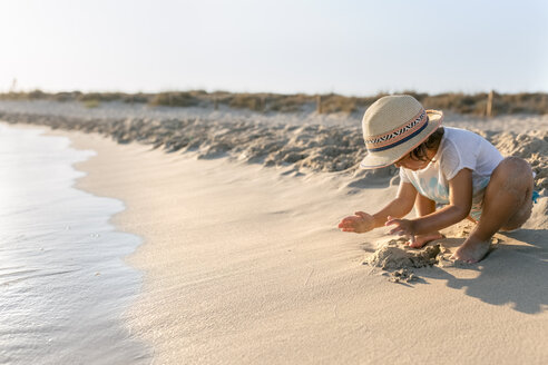 Spain, Menorca, little girl playing on the beach - MGOF03159